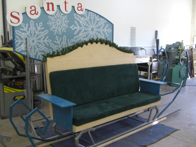 Santa's sleigh: steel sleigh rails, wooden bench, foam pads with custom covers, and sign with vinyl graphics.